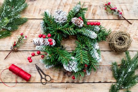Machen Sie Weihnachtskranz. Fichtenzweige, Kegel, Threads, Schnur, Sciccors auf Draufsicht des hellen hölzernen Hintergrundes Standard-Bild - 92346520