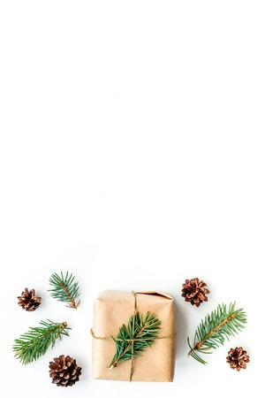 Gifts for new year wrapped in craft paper near spruce branches and cones on white background top view copyspace