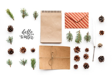 Write greetings. Envelope, paper, spruce branches and cones and hello winter hand lettering on white background top view pattern
