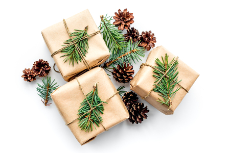 Gifts for new year wrapped in craft paper near spruce branches and cones on white background top view