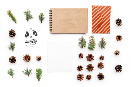 Write greetings. Envelope, paper, spruce branches and cones and hello winter hand lettering on white background top view pattern copyspace