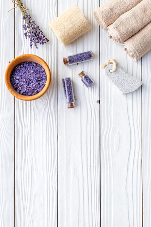 Set for foot spa with lavender. Flowers, spa salt, pumice stone, soap on white wooden background top view copyspace