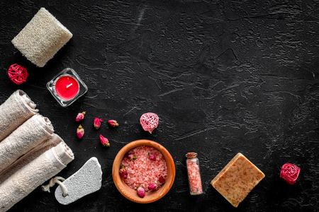 Romantic set for foot spa. Candles, salt, pumice stone, soap on black background top view copyspace Stock Photo