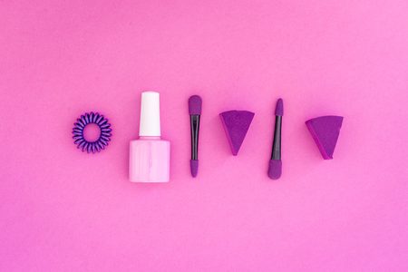 Cosmetics on colorful background. Pink nail polish and violet eyeshadow applicator on pink background top view copyspace Banco de Imagens