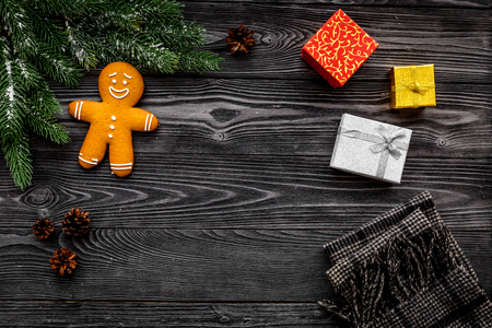 Christmas gifts. Wrapped boxes and gingerbread cookies near spruce branches on dark wooden background top view copyspace Zdjęcie Seryjne