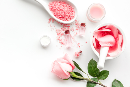 Make cosmetics with rose  oil. Mortar with rose petals and pestle on white background top view copyspace