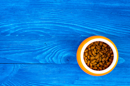 Pet food in bowl on blue wooden background top view copyspace Stock fotó - 90413407
