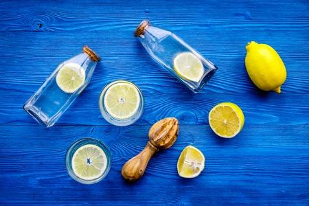 Fresh homemade lemonade. Lemons, juicer, glass for beverage on blue wooden background top view