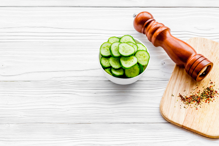 Slices of fresh cucumbers in the bowl near paperbox. White wooden background copyspace Stock Photo