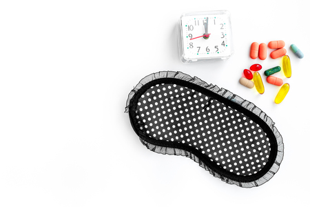Sleeping pills for insomnia near sleep mask and alarm clock on white background top view.