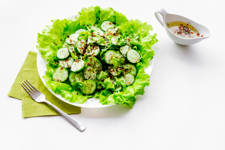 Salad with fresh cucumbers and lettuce near gravy boat. White background copyspace Stock Photo - 89615059