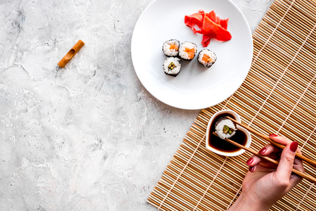 Hand takes sushi roll with salmon and avocado with chopstick. Grey stone and mat background top view copyspace