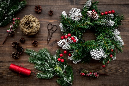 Make christmas wreath. Spruce branches, cones, threads, sciccors on wooden background top view
