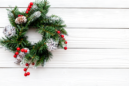 Christmas wreath woven of spruce branches with red berries on white wooden background top view copyspace