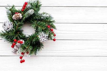 Weihnachtskranz gewebt von Fichtenzweigen mit roten Beeren auf weißem hölzernem Hintergrund Draufsicht copyspace Standard-Bild - 90423401