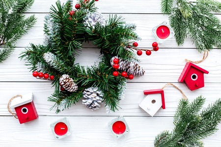 Decorate house for Christmas. Wreath and toys on white wooden background top view
