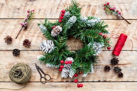 クリスマスリースを作ります。トウヒの枝、円錐、スレッド、ひも、sciccors に光木製の背景トップビュー