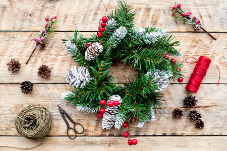 Make christmas wreath. Spruce branches, cones, threads, twine, sciccors on light wooden background top view Stock Photo