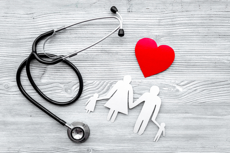 Choose health insurance. Stethoscope, paper heart and silhouette of family on grey wooden background top view Archivio Fotografico