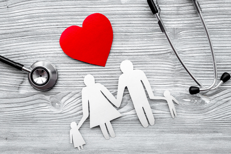 Choose health insurance. Stethoscope, paper heart and silhouette of family on grey wooden background top view Stock Photo