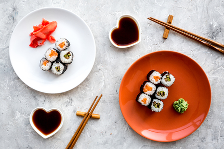 Sushi roll with salmon and avocado on plate with soy sauce, chopstick, wasabi on grey stone background top view