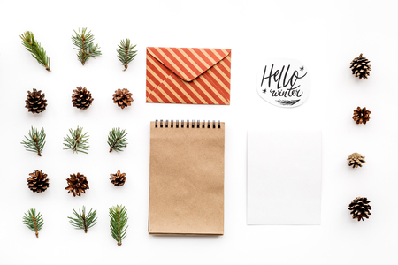 Write greetings. Envelope, paper, spruce branches and cones and hello winter hand lettering on white background top view.