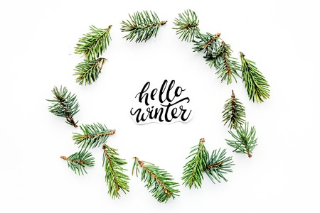 Hello winter hand lettering. Winter pattern with spruce branches on white background top view pattern Stok Fotoğraf