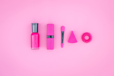 화려한 배경 화장품입니다. 밝은 분홍색 매니큐어, 립스틱, 분홍색 배경 위의 아이 섀도우 주걱. 스톡 콘텐츠 - 89580367