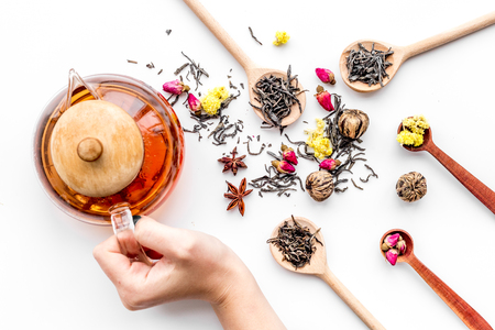 Brew tea with flowers and spices. Hand hold tea pot on white background top view Stock Photo