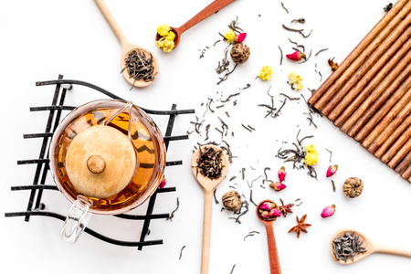 Brew tea with flowers and spices. Dried leaves and petals near tea pot on white background top view.