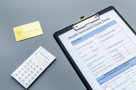 Take out health insurance. Document, bank card on dark grey background Stock Photo