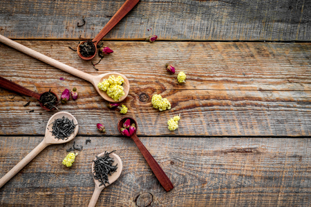 Dried tea leaves near supplements like flowers and spices on wooden background top view.