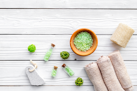 Foot spa cosmetics. Spa salt, pumice stone, soap and towel on white wooden background top view copyspace Stock Photo