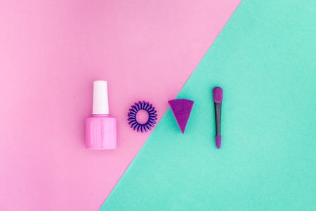 Cosmetics on colorful background. Pink nail polish and violet eyeshadow applicator on pink and mint background top view copyspace Banco de Imagens