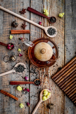 Brew tea with flowers and spices. Dried leaves and petals near tea pot on wooden background top view Stock Photo