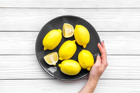 손을 신선한 레몬 접시를 잡아. 흰색 나무 배경 상위 뷰 copyspace
