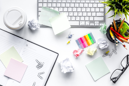 Clutter in office. Desk covered with crumpled paper and scattered stationery. White background top view
