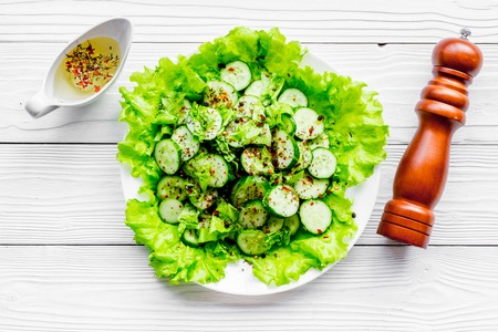 Salad with fresh cucumbers and lettuce near paperbox and gravy boat. Grey wooden background top view Stock Photo - 89695329