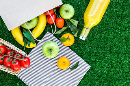 Fruit voor een picknick. Apple, banaan, mandarijn op groene gras hoogste mening als achtergrond copyspace Stockfoto