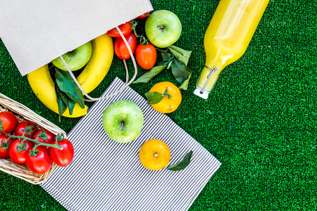 Fruits for picnic. Apple, banana, tangerine on green grass background top view copyspace