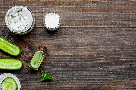 Cucumber moisturising cream or mask. Dark wooden background top view copyspace Banco de Imagens