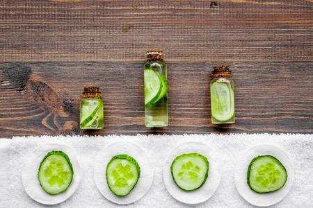 Lotion with cucumber pattern. Dark wooden background top view copyspace