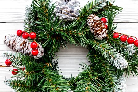 Weihnachtskranz gesponnen von den Fichtenzweigen mit roten Beeren auf Draufsicht der weißen hölzernen Draufsichtnahaufnahme Standard-Bild - 90469382