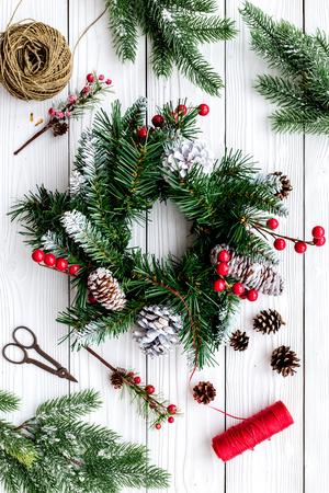 Machen Sie Weihnachtskranz. Fichtenzweige, Kegel, Threads, Schnur, Sciccors auf Draufsicht des weißen hölzernen Hintergrundes Standard-Bild - 89695181