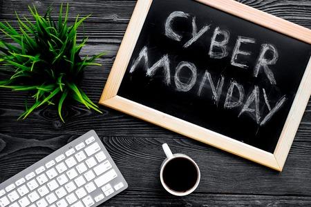 Words cyber monday written on blackboard near keyboard on grey wooden background top view