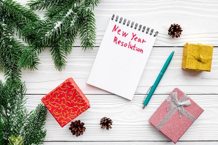 Resolución del año Nuevo. Cuaderno entre cajas de regalo y rama de abeto en la vista superior de fondo blanco de madera