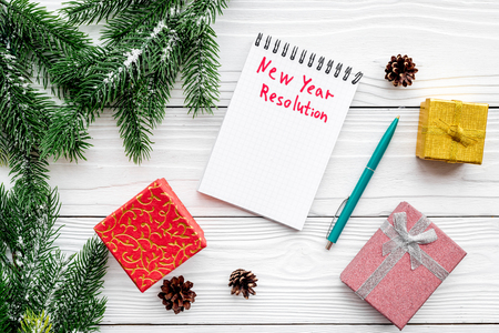 New year resolution. Notebook among gift boxes and spruce branch on white wooden background top view