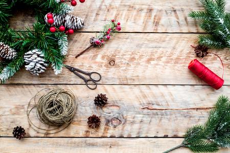 Machen Sie Weihnachtskranz. Fichtenzweige, Kegel, Threads, Schnur, Sciccors auf Draufsicht des hellen hölzernen Hintergrundes Standard-Bild - 90449018
