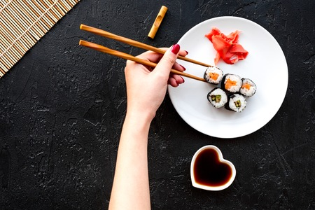 Hand takes sushi roll with salmon and avocado with chopstick. Black background top view