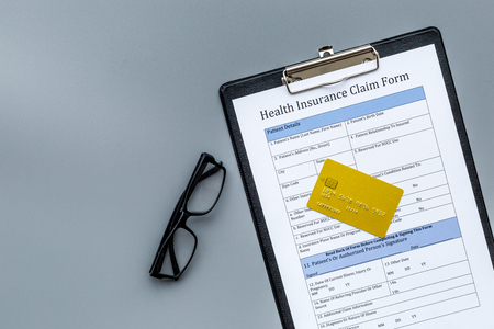 Buy health insurance. Document, bank card on dark grey background top view copyspace Stock Photo